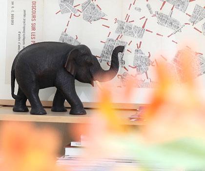 Bücherregal mit Elefantenfigur und Karte der Situationisten