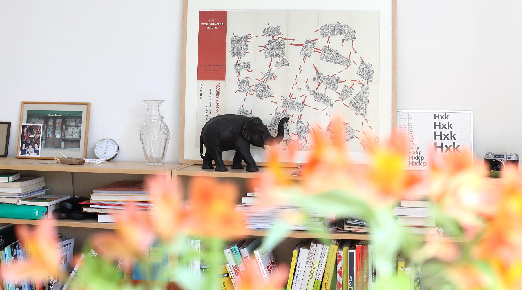 Innenansicht Agentur, Bücherregal mit einer Karte der Situationisten: Psychogeographic guide of Paris, sowie Vase, Hydrometer und Bilderrahmen.