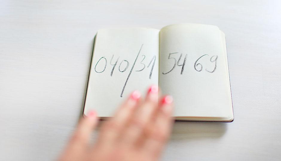 aufgeschlagenes Notizheft mit der Telefonnummer von IconScreen: 040 315469; eine Frauenhand liegt auf dem Notizheft