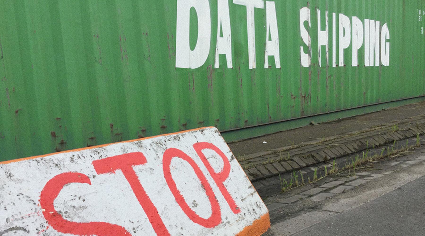 Poller mit der Aufschrift STOP vor einem Container im Hamburger Hafen mit der fingierten Aufschrift DATA SHIPPING