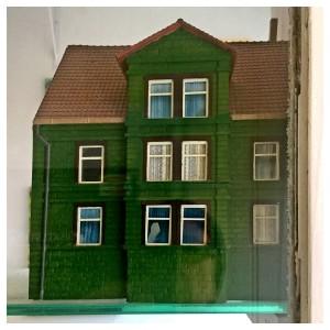 ein Haus in dem Schaufenster des Antiquitätengeschäftes von Rainer Mauersberg in Nienburg in der Bisquitstraße 2