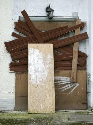 eine zugebretterte Tür, oben drüber eine  Kippenberger-Lampe