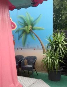 eine verträumte Ecke auf dem Hamburger Dom, hinter dem Fahrgeschäft finden sich 2 Plastik-Stühle unter einer gemalten Palme