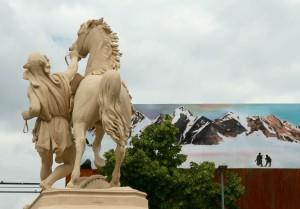Pferd und Reiter Statue auf dem Hamburger Dom, im Hintergrund ein gemates Alpenpanorama