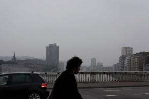 ein trauriger nebeliger Tag in Lüttich, ein fahrradfahrer im Profil quert eine Brücke über die Maas