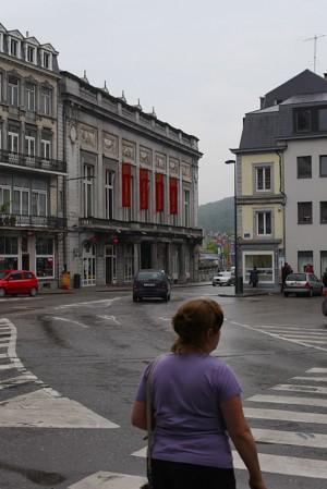 EIne Frau mit einem lila Shirt überquert eine Starße im belgischem Kurort Spa