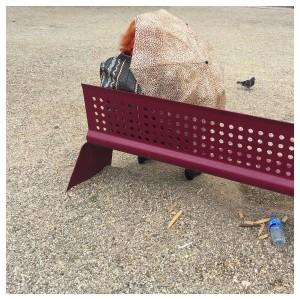 eine rothaarige Frau sitz auf einer Bank im Park und schütz sich gegen den Wind mit einem Regenschirm, der sich mit einem ähnlichen Muster wie der Schotter unter der Bank darstellt, skurril